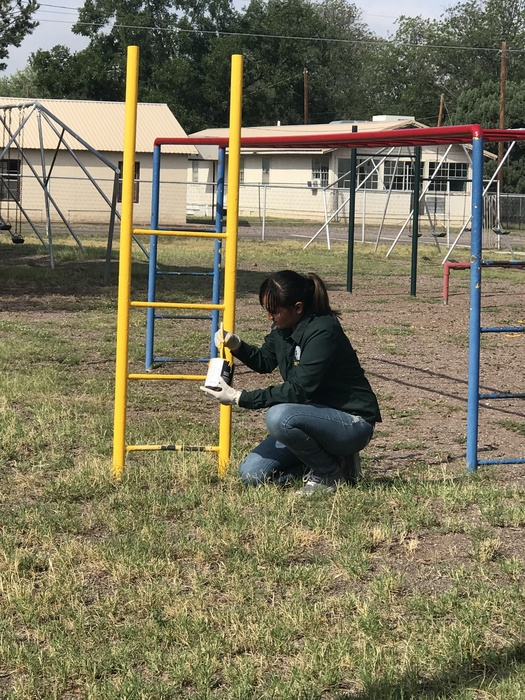 Ms. Ramos painting the playground equipment.