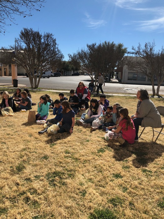 Students have a picnic on the lawn while listening to readers